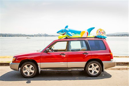 Car with beach toys and floaties on the roof parked by a lake Stock Photo - Premium Royalty-Free, Code: 673-08139167