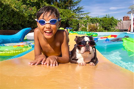 Boy and his Boston Terrier wearing matching goggles float on a toy in a pool Stock Photo - Premium Royalty-Free, Code: 673-08139175