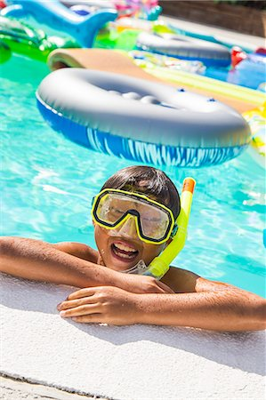 preteen boy shirtless - Boy wearing a scuba mask and snorkel swims in a pool full of inflatable toys Stock Photo - Premium Royalty-Free, Code: 673-08139184