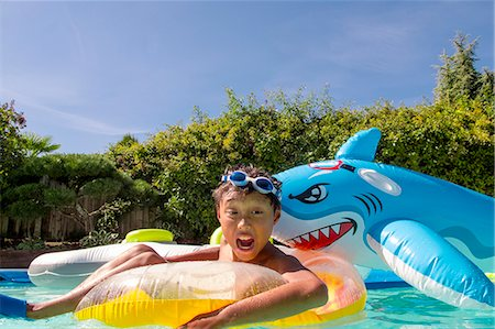 preteen boy shirtless - Boy pretends to be attacked by an inflatable shark in a pool Stock Photo - Premium Royalty-Free, Code: 673-08139180