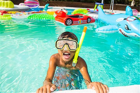 preteen boy shirtless - Boy wearing a scuba mask and snorkel swims in a pool full of inflatable toys Stock Photo - Premium Royalty-Free, Code: 673-08139183