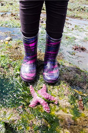 preteen girl feet - Child's feet in boots standing by a sea star Stock Photo - Premium Royalty-Free, Code: 673-08139199