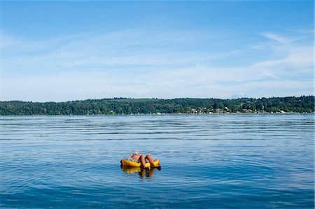 preteen boy shirtless - Boy floats in a floatie ring in Puget sound Stock Photo - Premium Royalty-Free, Code: 673-08139204