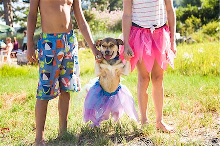 preteen boy shirtless - Small dog in a tutu with his paws held up by children Stock Photo - Premium Royalty-Free, Code: 673-08139206