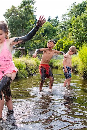 Children playing in a muddy creek Stock Photo - Premium Royalty-Free, Code: 673-08139201