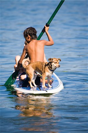preteen boy shirtless - Children and a dog on a paddle board Stock Photo - Premium Royalty-Free, Code: 673-08139203