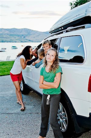 Woman kissing a man through a car window in front of their kids Stock Photo - Premium Royalty-Free, Code: 673-08139216