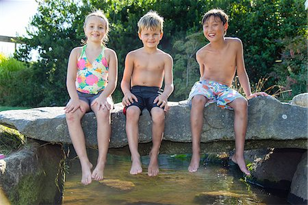 preteen girl topless - Three children sitting on a stone bridge over a small creek Stock Photo - Premium Royalty-Free, Code: 673-08139233