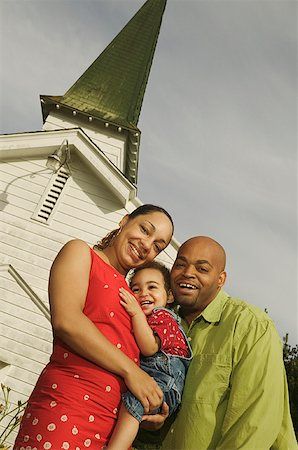 A family standing close together in front of white church. Stock Photo - Premium Royalty-Free, Code: 673-02137626