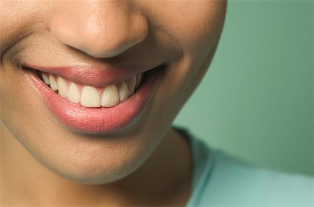 Tight shot of a young woman's smile. Stock Photo - Premium Royalty-Free, Code: 673-02137648
