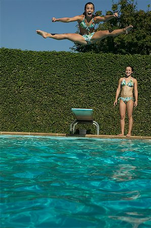 Twin girl watches her sister leap from a diving board. Stock Photo - Premium Royalty-Free, Code: 673-02137744
