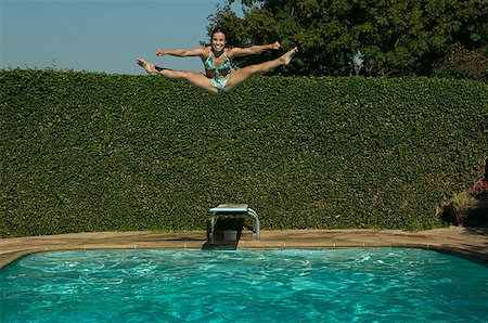 Teenage girl does the splits while jumping into a swimming pool. Stock Photo - Premium Royalty-Free, Code: 673-02137745