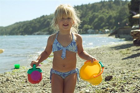 Young girl holding beach toys. Stock Photo - Premium Royalty-Free, Code: 673-02137927