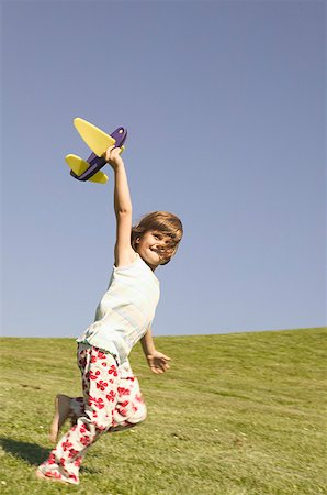 Young girl holding a toy airplane. Stock Photo - Premium Royalty-Free, Code: 673-02137963