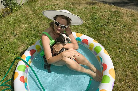 dog in heat - Woman sitting with her dog in backyard baby pool. Stock Photo - Premium Royalty-Free, Code: 673-02138073