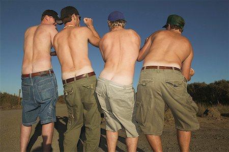 Rear view of four shirtless men dancing. Stock Photo - Premium Royalty-Free, Code: 673-02138096