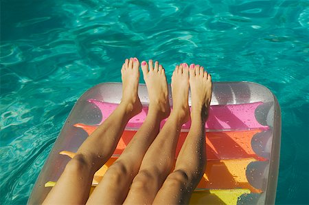 Two pairs of girls' legs on a raft. Stock Photo - Premium Royalty-Free, Code: 673-02138196