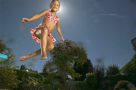Young girl jumping into a pool. Stock Photo - Premium Royalty-Free, Code: 673-02138200