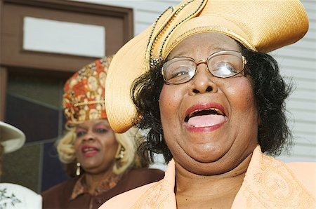 Senior women wearing hats and singing on church steps. Stock Photo - Premium Royalty-Free, Code: 673-02138496