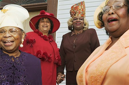 Four senior women wearing hats and singing on church steps. Stock Photo - Premium Royalty-Free, Code: 673-02138497