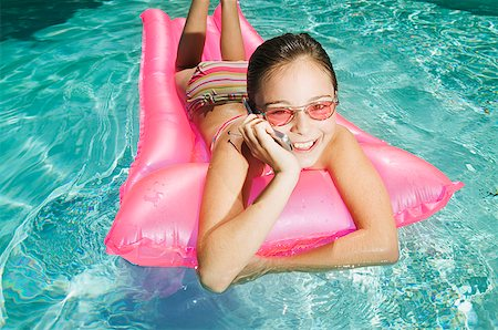 A girl floating in a pool while chatting on a mobile phone Stock Photo - Premium Royalty-Free, Code: 673-02138710