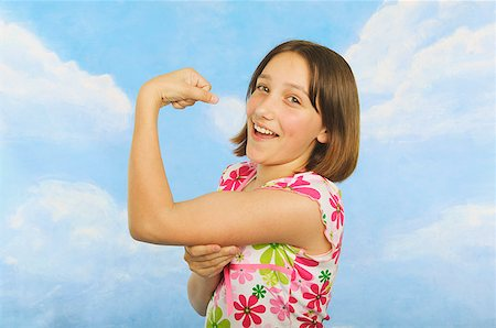 A teenaged girl flexing her muscles Stock Photo - Premium Royalty-Free, Code: 673-02138882
