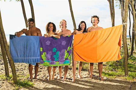 Men and women hiding behind beach towels Stock Photo - Premium Royalty-Free, Code: 673-02139140