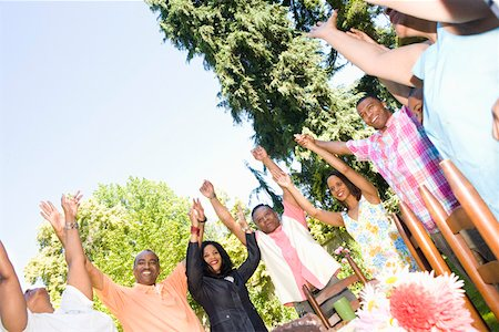 Family with upraised arms at picnic Stock Photo - Premium Royalty-Free, Code: 673-02139616