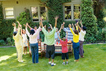 Family with upraised arms at picnic Stock Photo - Premium Royalty-Free, Code: 673-02139610
