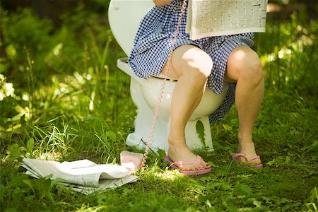 Woman sitting on toilet in grass Stock Photo - Premium Royalty-Free, Code: 673-02140000