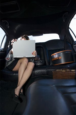 sexy women legs - Woman using laptop in luxury car Stock Photo - Premium Royalty-Free, Code: 673-02140114