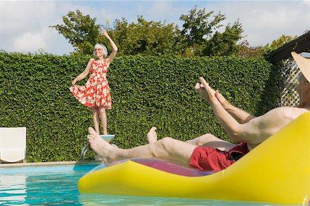 Senior couple having poolside fun Stock Photo - Premium Royalty-Free, Code: 673-02140194