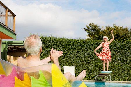 Senior couple having poolside fun Stock Photo - Premium Royalty-Free, Code: 673-02140195