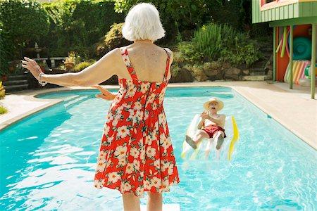 Senior couple having poolside fun Stock Photo - Premium Royalty-Free, Code: 673-02140196