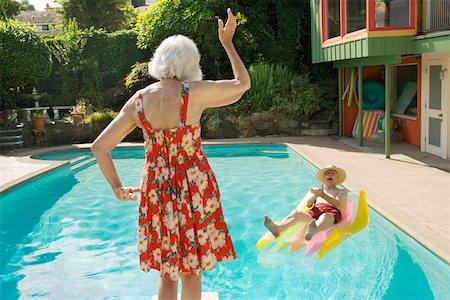 Senior couple having poolside fun Stock Photo - Premium Royalty-Free, Code: 673-02140198