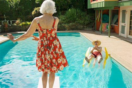 Senior couple having poolside fun Stock Photo - Premium Royalty-Free, Code: 673-02140192