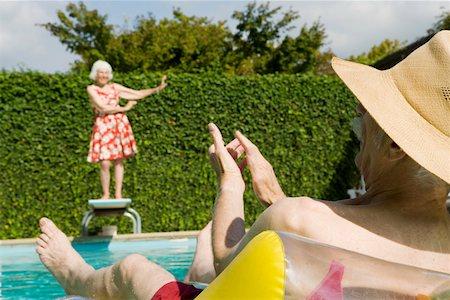 Senior couple having poolside fun Stock Photo - Premium Royalty-Free, Code: 673-02140193