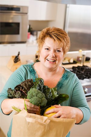 Woman with bag of produce in kitchen Stock Photo - Premium Royalty-Free, Code: 673-02140398