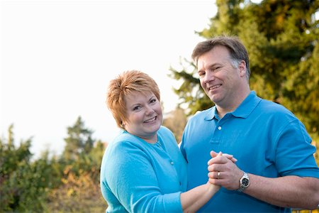 Portrait of middle aged couple dancing outside Stock Photo - Premium Royalty-Free, Code: 673-02140423
