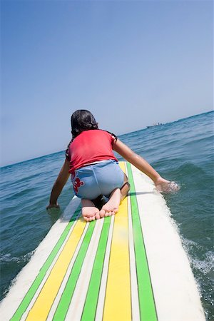 Young girl paddling surfboard Stock Photo - Premium Royalty-Free, Code: 673-02140740
