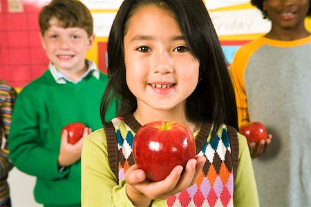 Portrait of girl holding apple in classroom Stock Photo - Premium Royalty-Free, Code: 673-02141894