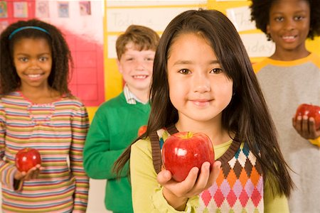Portrait of girl holding apple in classroom Stock Photo - Premium Royalty-Free, Code: 673-02141895