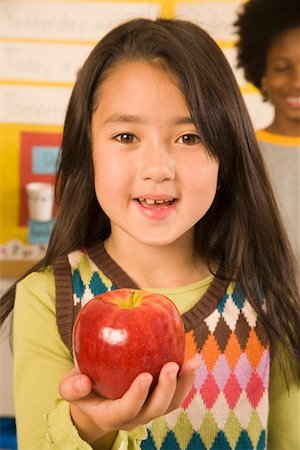 Portrait of girl holding apple in classroom Stock Photo - Premium Royalty-Free, Code: 673-02141896