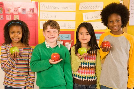 Portrait of children holding apples in classroom Stock Photo - Premium Royalty-Free, Code: 673-02141892