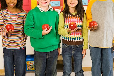 Portrait of children holding apples in classroom Stock Photo - Premium Royalty-Free, Code: 673-02141893