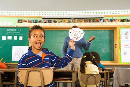 Boy holding drawing over teacher's face Stock Photo - Premium Royalty-Free, Code: 673-02141914