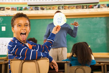 Boy holding drawing over teacher's face Stock Photo - Premium Royalty-Free, Code: 673-02141911