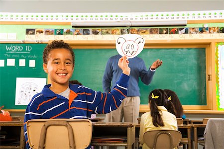photo of class with misbehaving kids - Boy holding drawing over teacher's face Stock Photo - Premium Royalty-Free, Code: 673-02141913
