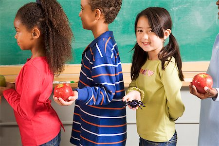 Girl holding spider in line to give apples to teacher Stock Photo - Premium Royalty-Free, Code: 673-02141920