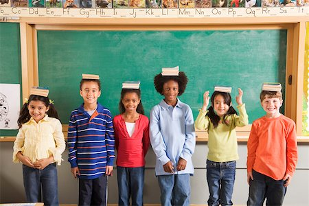 Row of students with books on their heads in classroom Stock Photo - Premium Royalty-Free, Code: 673-02141921